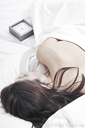 Sleeping woman in white sheets with a clock