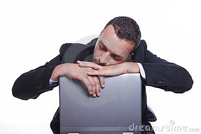 Sleepy businessman with his laptop taking break