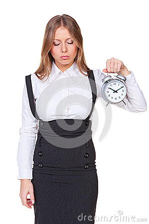 Sleepy businesswoman holding alarm clock