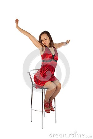 Sleepy girl in red dress sitting on the chair