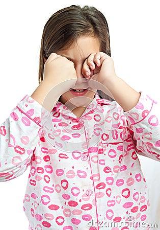 Sleepy girl wearing pajamas isolated on white