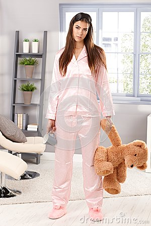 Sleepy woman in pyjama with teddy bear