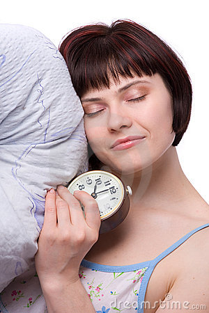 Sleepy woman is sleeping and holding alarm clock