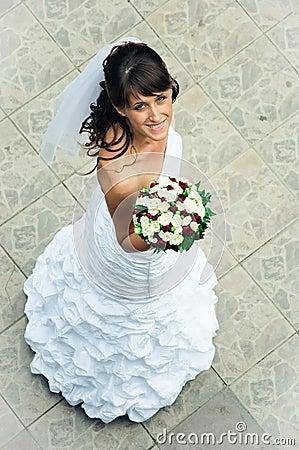 Slender bride with a bouquet look upwards