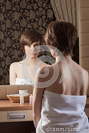 Slender brunette in towel posing near mirror