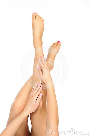 Slender naked female  legs being massaged isolated