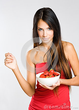 Slender young brunette holdng strawberries.