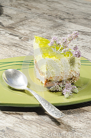 Slice of lime cheesecake decorated with mint flowers, blurred background