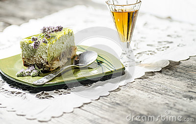 Slice of lime cheesecake decorated with mint flowers and glass of cognac, blurred background