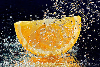 Slice of orange with stopped motion water drops