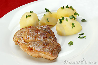 Slice of roast pork with boiled potatoes