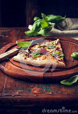 Slice of rustic pizza topped with fresh basil