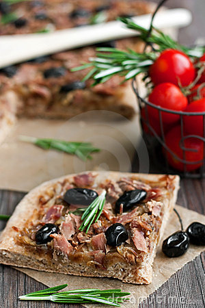 Slice of tuna tart with olives and onions