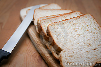 Sliced bread with knife and cutting board.