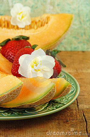 Free Sliced Cantaloupe, Strawberries, And Flowers. Stock Images - 9351894