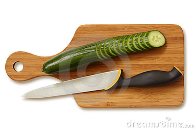 Sliced cucumber and knife on cutting board.