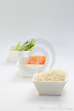 Sliced cucumber raw salmon and rice in white dish