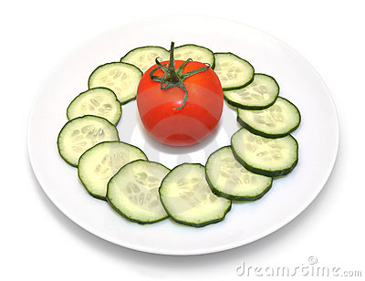 Sliced cucumbers and tomato on white plate