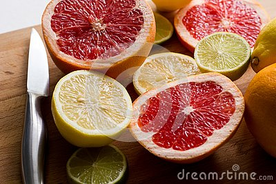 Sliced fresh citrus lemons, limes, grapefruits on a wooden board with a metal knife, side view Stock Photo