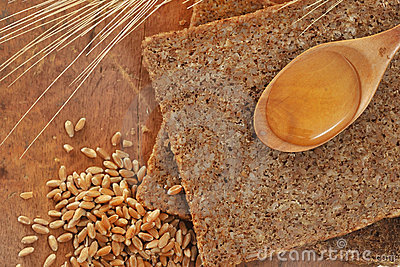 Sliced integral bread and honey spoon