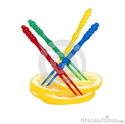 Sliced lemon and multicolored plastic skewers