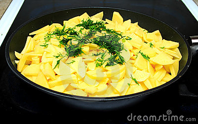 Sliced raw potatoes on frying pan