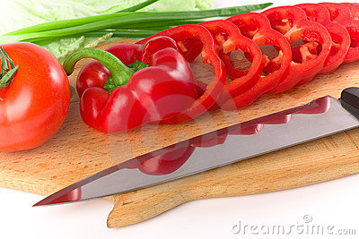 Sliced red ripe fresh pepper on cutting board