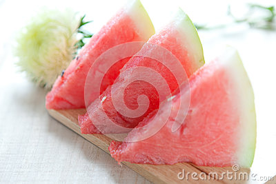 Sliced ​​ripe red watermelon on a wooden