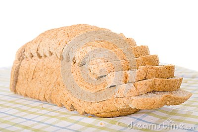 Sliced wholemeal brown bread placed on linen cloth