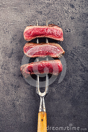 Free Slices Of Sirloin Beef Steak On Meat Fork On Concrete Background Stock Photography - 68410632
