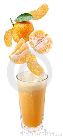 Slices of tangerine falling into a glass of fresh