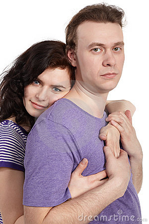 Slightly smiling woman embraces man from behind Stock Photo