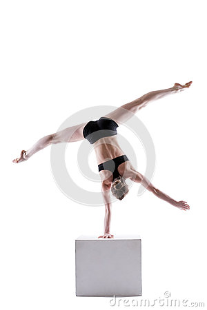Slim acrobat balancing on cube in studio