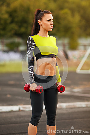 Free Slim Athletic Woman With Dumbbells In The Stadium. Sporty Sexy Girl With Flat Belly Workout, Outdoors Royalty Free Stock Images - 61502589