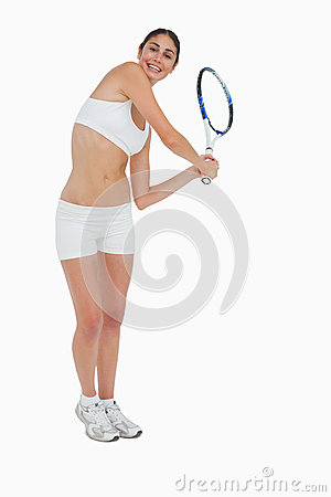 Slim brunette playing tennis in white clothes