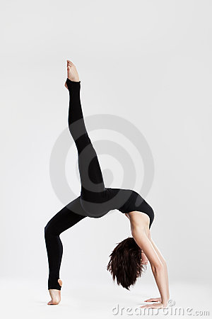 Slim dancer in yoga pose bending backwards