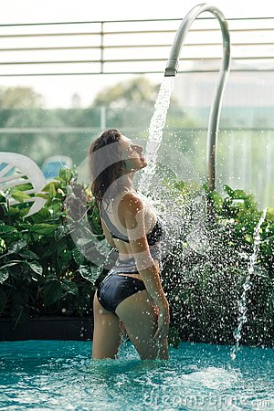 Free Slim Female In Swimsuit Takes Shower In Swimming Pool Between Green Bushes On Rooftop With City Scape Background Stock Photos - 138232853