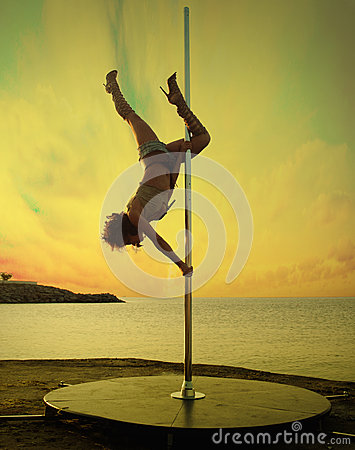 Slim girl exercise pole dance on a sunset sea landscape.