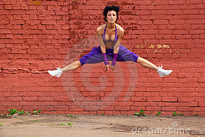 Slim girl jumps on background of wall
