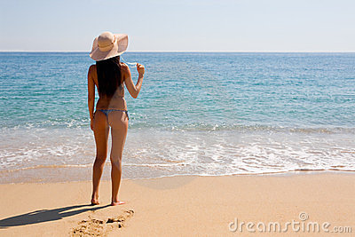 Slim girl standing by sea