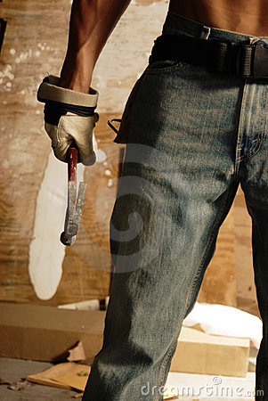 Slim male in jeans with hammer