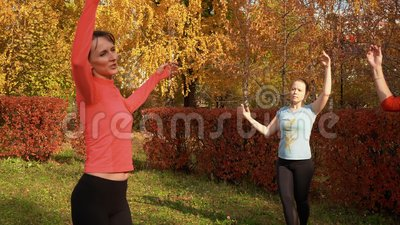 Slim woman practising port de bras exercise in colorful park at autumn day. Fitness woman training on dance class. Outdoor. Sport woman training choreography in stock video