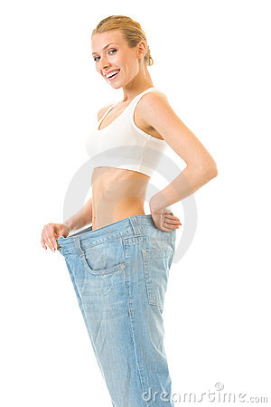 Slim woman trying on old jeans