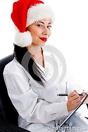 Slimme arts in Kerstmishoed het schrijven voorschrift