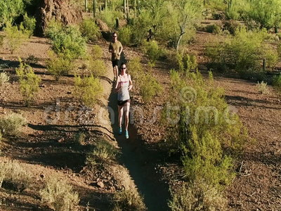 Slow Motion Aerial Shot of Trail Runners in Arizona Sonoran Desert Surrounded by Saguaros. Slow Motion Aerial Shot of Trail Runners in Rugged Arizona Sonoran stock video