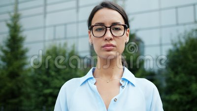 Slow motion of confident business lady in formal clothing standing outdoors alone. Slow motion of confident business lady in formal clothing and trendy glasses stock video