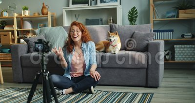 Slow motion of female vlogger recording video at home with cute dog. Slow motion of female vlogger attractive young lady recording video at home with cute dog stock video footage