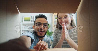 Slow motion of girl and guy opening carton box taking gift laughing having fun. Slow motion of surprised girl and guy opening carton box taking gift laughing stock footage