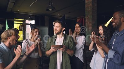 Slow motion of handsome bearded man blowing candles on birthday cake at office party with colleagues clapping hands and. Congratulating him. Holidays, people stock footage