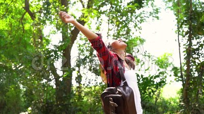 Slow motion - Happy young Asian woman traveler with backpack walking in forest. Hiker Asian woman with backpack walking on path in summer forest. Adventure stock video